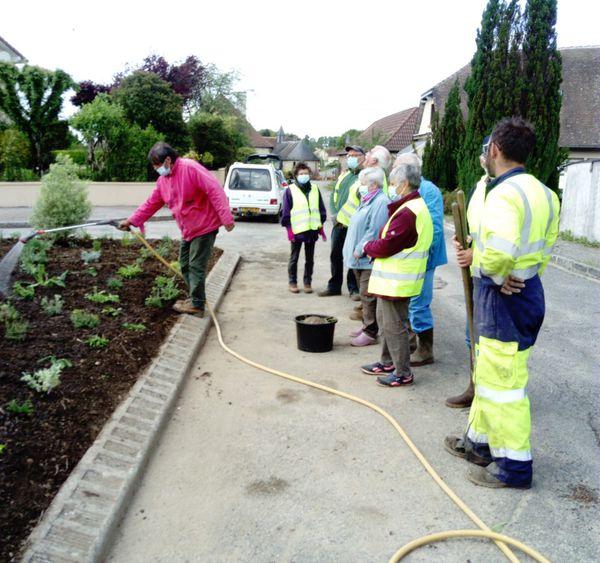 Les bénévoles au travail sur les nouveaux massifs de fleurs à Saint Hilaire les Places.